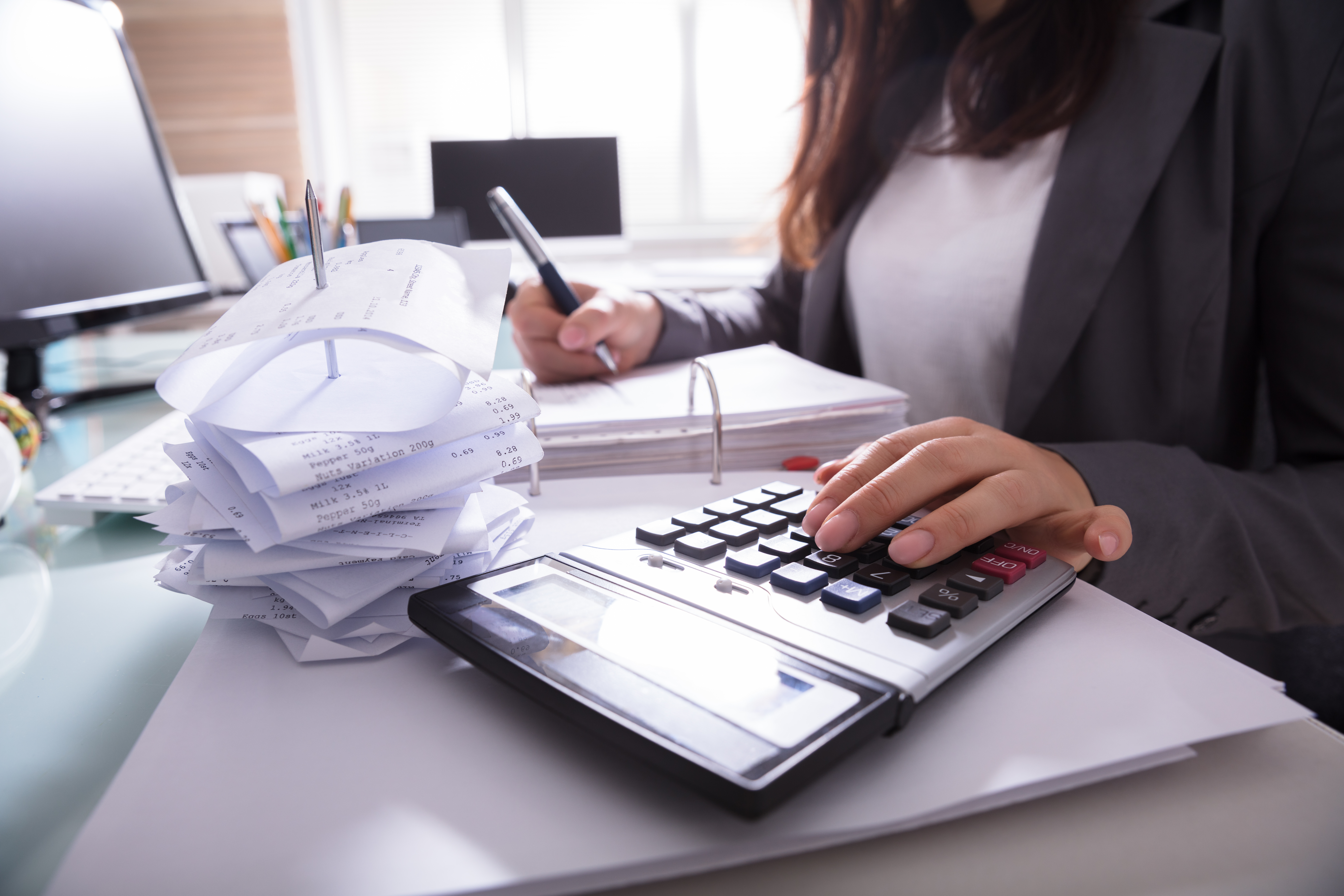 Close-up Of A Businesswoman's Hand Calculating Invoice With Calculator